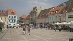 People walking and old buildings at the Council Square, Brasov Stock Footage