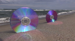 Two CDs on sea beach sand and waves Stock Footage