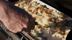 A man cooks potato hash browns while camping Stock Footage