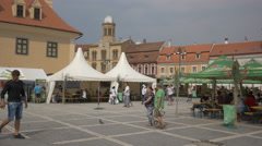 People sitting at tables in the Council Square, Brasov Stock Footage