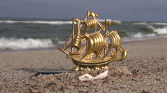 Seascape with decorative toy brass  ship in sand Stock Footage