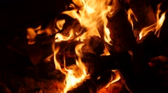 A shot of a large campfire burning at night in camp Stock Footage