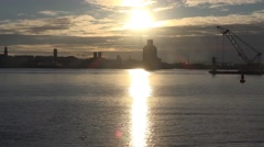 4k romantic sun set on sea with silhouette of buildings and industrial crane Stock Footage