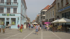 People walking on Republicii street and into the Council Square, Brasov Stock Footage
