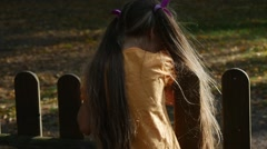 Girl Long Fair Hairs is Trying to Climb on The Wooden Fence Cannot Climb Going - stock footage