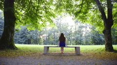 Woman in park sit on bench between two trees 4K - stock footage