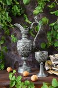 Antique pitcher and a goblet as well as walnuts on a dark background Stock Photos