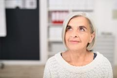 Thoughtful Senior Office Woman Looking Up - stock photo