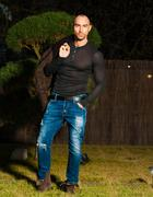 Attractive young muscular man in brown leather jacket, black shirt, blue jeans - stock photo