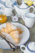 A light breakfast consisting of a cup of tea and croissants with a jam - stock photo