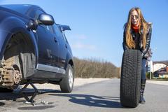 Female biker rolls big wheel Stock Photos