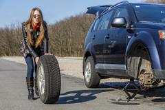 Female driver repairs car Stock Photos