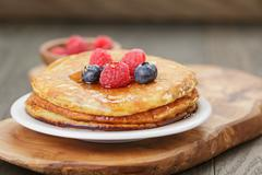 Pancakes with raspberry, blueberry and maple syrup - stock photo