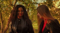 Friends girls caucasian and african walking in park talking smiling slow motion. Stock Footage