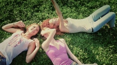 Friends, girls, caucasians, having fun outdoors, laying on grass, slow motion. - stock footage