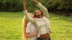 Friends,  girls caucasian and african walking in park making selfie slow motion. Stock Footage