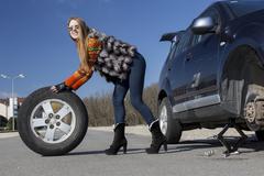Leggy beautiful female holds big wheel Stock Photos