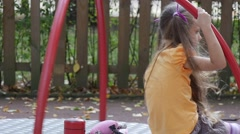 Girl is Swinging on Carousel with Toy Rabbit Pink Tilda Little Girl With Long Stock Footage
