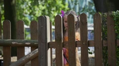 Girl Have Entered to The Yard by Door in Wooden Fence Little Girl With Long Stock Footage