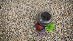 Glass bottle on rocky ground top view Stock Footage