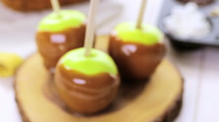 Apples freshly dipped in caramel on cutting board. - stock footage