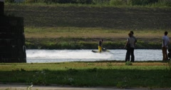 Four People Are Standing at The River Bank And Looking at Water Motobike and Stock Footage