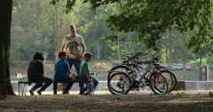 Family People are Sitting at the Bench in Park People Have a Rest Bicycles are Stock Footage