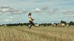 Pretty young woman walking in a hay field playing guitar. Stock Footage
