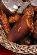 Pork ham and sausages placed in a wicker basket Stock Photos