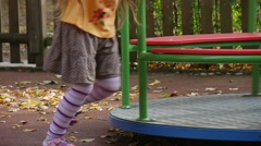 Little Girl in Orange T-Shirt and Skirt Legs Close Up Is Rotating The Carousel Stock Footage
