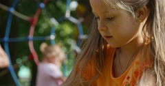 Little Girl With Long Fair Hairs in Orange T-Shirt is Jumping Playing Outdoors - stock footage