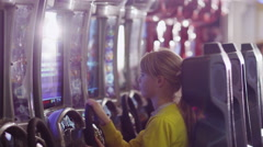 Girl is Playing Racing Arcade Video Game at Entertainment - stock footage