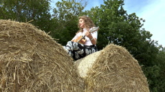 Pretty young woman playing guitar, sitting on a hay roll. Stock Footage