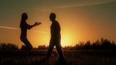 Girl run to guy who hugs her and spins around on sunset Stock Footage