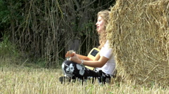 Pretty young woman playing guitar, sitting against a hay roll. Stock Footage