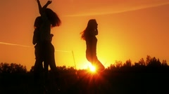 Friends, girls enjoy nature running, jumping in fields on sunset, slow motion Stock Footage