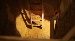 Ladder leading down to an underground hand dug tunnel Stock Footage