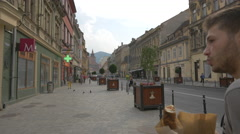 Tourists walking and driving cars on Muresenilor street, Brasov Stock Footage
