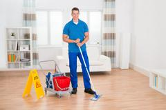 Happy Worker With Cleaning Equipments And Wet Floor Sign In House Stock Photos