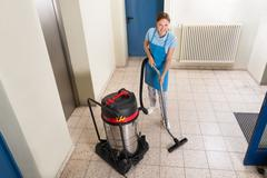 Young Female Janitor Cleaning Floor With Vacuum Cleaner Stock Photos