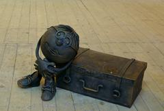 Iron little man and suitcase Stock Photos