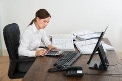 Young Female Accountant Doing Calculation With Calculator At Desk - stock photo