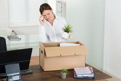 Young Sad Businesswoman Putting Her Belongings In Box At Wooden Desk - stock photo
