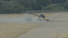 Stock Video Footage of Combine harvester and tractor at work on wheat.