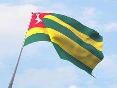 Stock Illustration of Togo flag flying on clear sky.