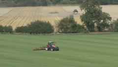 Stock Video Footage of Mowing turf with wheat harvest beyond.