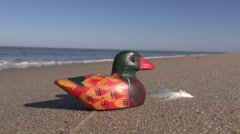 Seascape with decorative wooden duck in sand Stock Footage