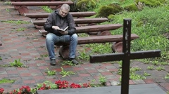 Man on bench with the Bible at outdoors church Stock Footage