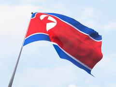 North Korea flag flying on clear sky. - stock illustration