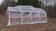 Men covering greenhouse in spring garden with polyethylene Stock Footage